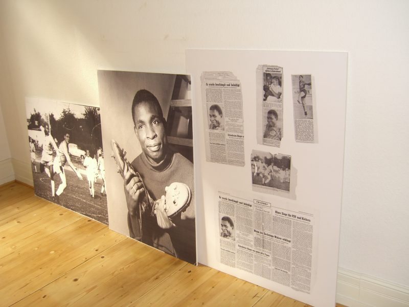 "Denise Mawila's title, ""Dieses Paar Schuhe"" (""this pair of shoes"") 2006, could've been said by Adolphe Mawila as he was being photographed by the Frankfurter Rundschau holding up his pair of German soccer shoes in 1964. The installation entails MDF boards covered with enlarged black and white photographs and texts, which overlap each other, leaned up against the wall."