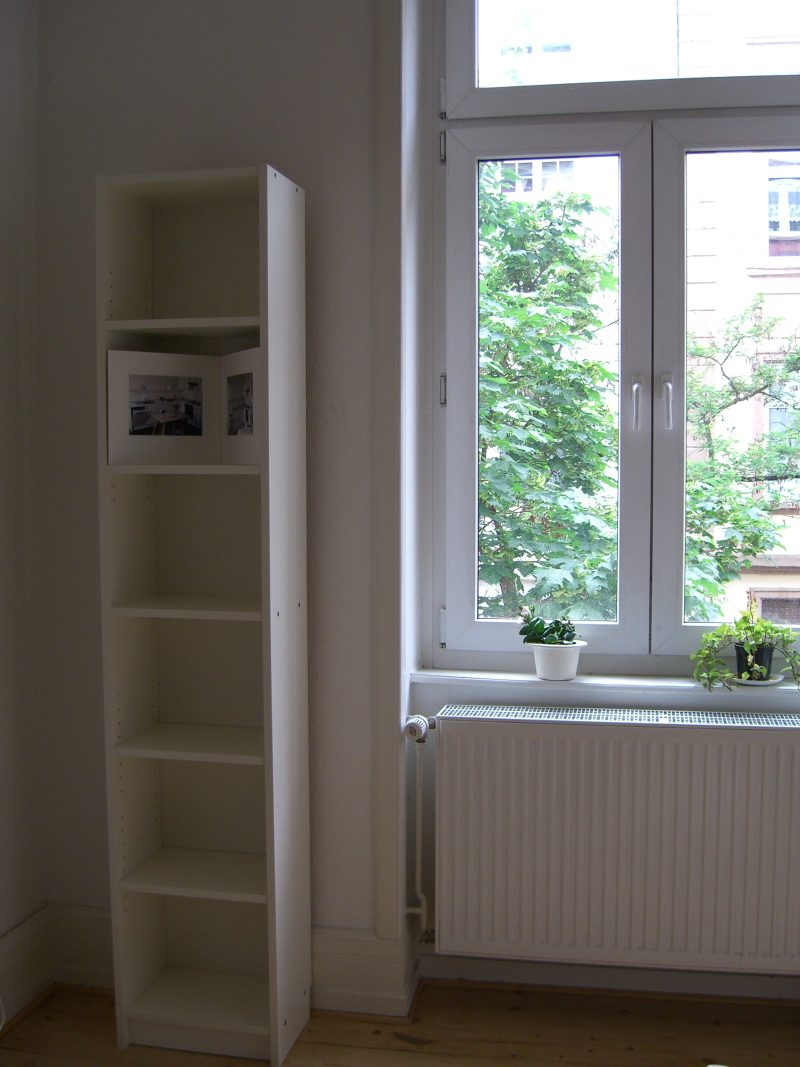 Anna Ostoya's installation contains two photographs taken by the artist, Hanna Hildegard, of Ostoya's former kitchen. The viewer peers into the depth of the bookshelf to see the private space of the place where Ostoya once worked and lived. Comparing the two portraits-like photos and the different staged living situations of the same environment.