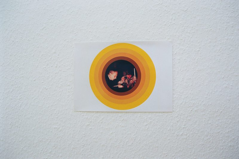A picture of a couple eating a candlelight dinner is framed with many colored bands in shades of gold and yellow. The photograph of the man and woman takes the circular shape of halo-like rings, which mark the significance of this banal yet vital moment. Is this a modern icon in a Renaissance tondo form? Are there traces of a higher power present in which we are witnessing this process of identification? Who is this couple and what is their significance?